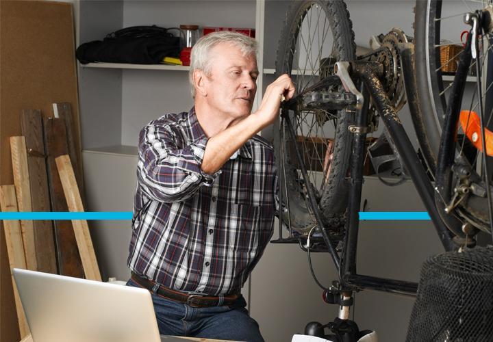 Man repairing a bike in his garage.