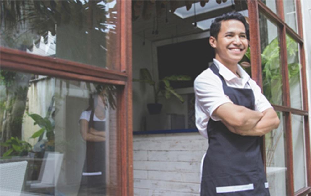 Business man standing in doorway to his cafe.