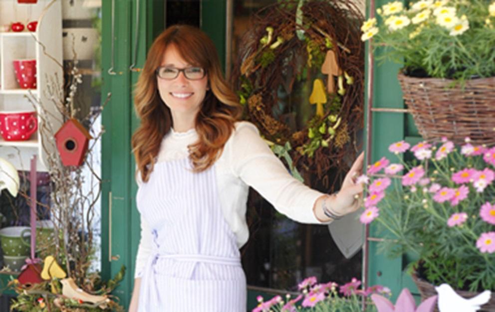 Woman standing outside flower shop.