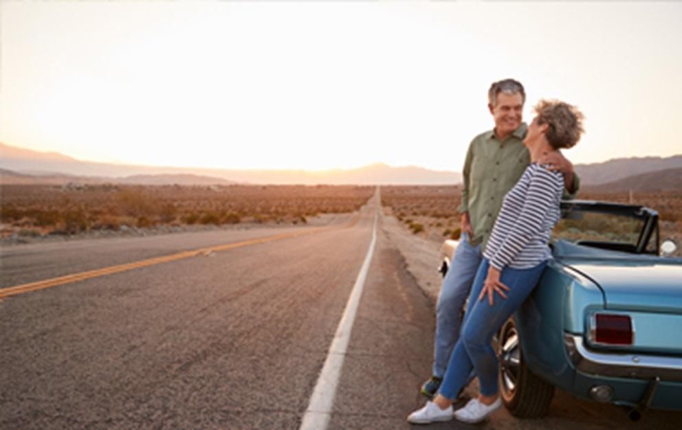 Man and woman leaning against classic car.