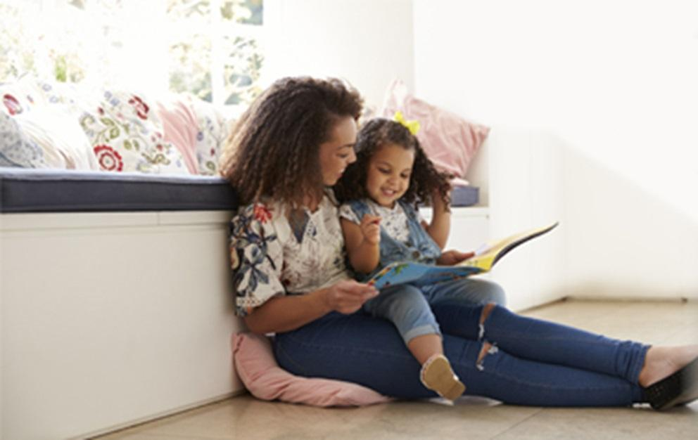 Mother reading a book to her toddler.