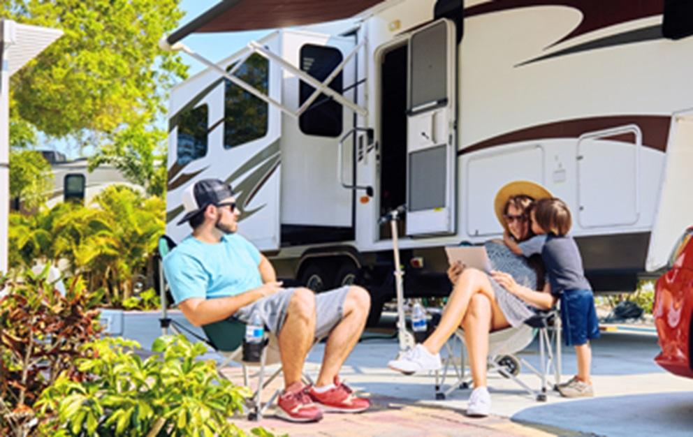 Family relaxing next to an RV