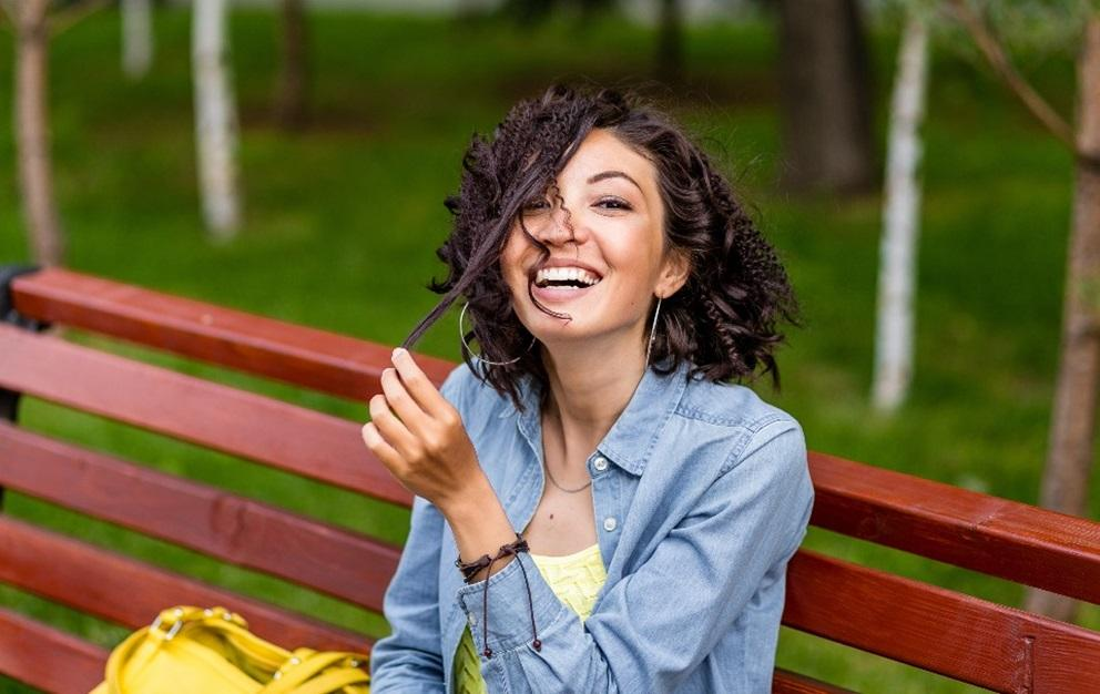 Woman playing with hair and sitting on a park bench